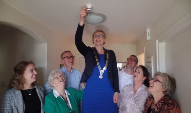 Bewoonster Anneke van Diest (tweede links) kijkt goedkeurend toe hoe burgemeester Marianne Besselink een bewegingssensor in haar woning installeert. Foto: Jan Hendriksen