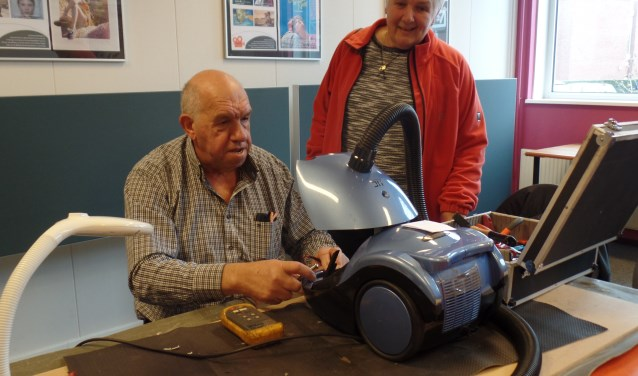 Karel Thus repareert de kapotte stofzuiger van Jeannette van der Heij. Foto: Jan Hendriksen.