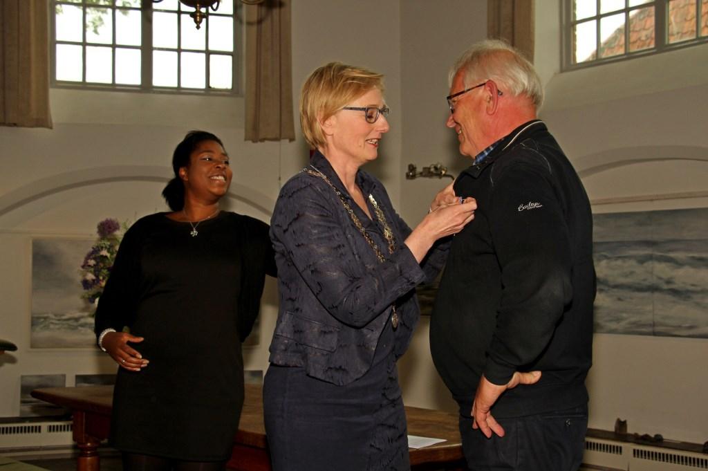 Hans Klompenhouwer krijgt de versierselen, Lid in de Orde van Oranje-Nassau opgespeld door burgemeester Besselink. Foto: Liesbeth Spaansen  © Achterhoek Nieuws b.v.