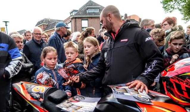 De Duitse coureur Didier Grams deelt handtekeningenkaarten uit aan de Hengelose jeugd. Foto: Luuk Stam