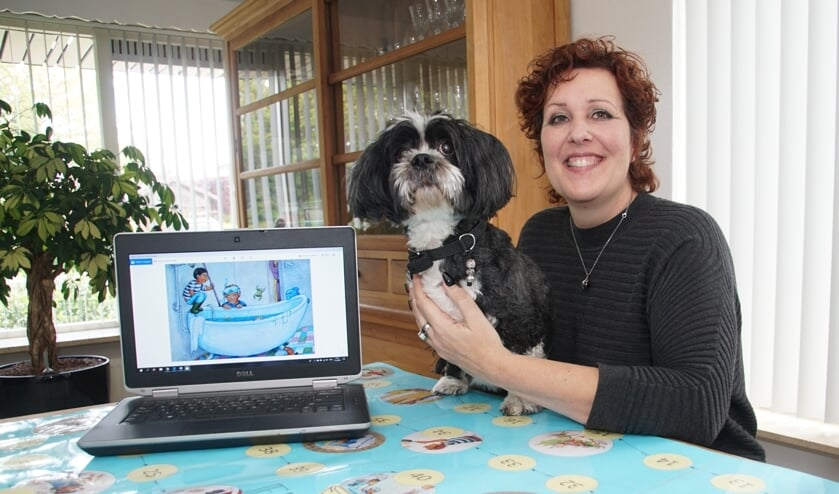 Bettina IJzendoorn, met een afbeelding van het boek op de pc, en met haar hond, die in een verhaal Guusje heet. Foto: Frank Vinkenvleugel
