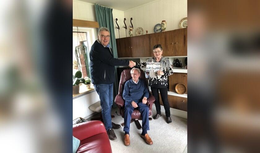 Medewerker Franko reikt het boekje uit aan de heer en mevrouw Ruesink. Foto: PR