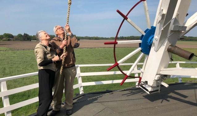 Wethouder Marijke van Haaren zet met molenaar Bennie Mensink de molen in werking. Nationale Molendag in Neede is met deze handeling geopend. Foto: PR
