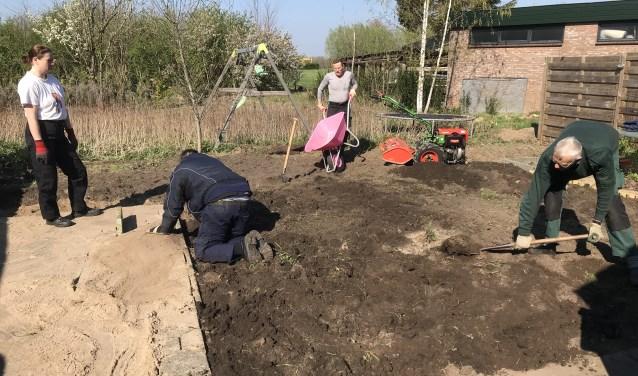 Wethouder en vrijwilligers aan het werk in de tuin. Foto: Present Bronckhorst  © Achterhoek Nieuws b.v.