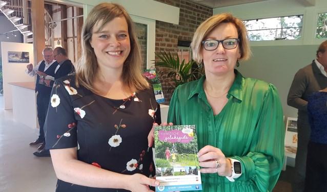Meike Prollius (l), toeristisch coördinator van de gemeente Oost Gelre, en wethouder Marieke Frank met de nieuwe Geluksgids. Foto: Kyra Broshuis