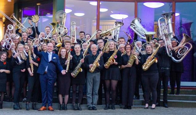 Muzikanten en oud-muzikanten van Unity, het opleidingsorkest van Eendracht, met hun dirigent Gerd Wensink. Foto Anouk Kots