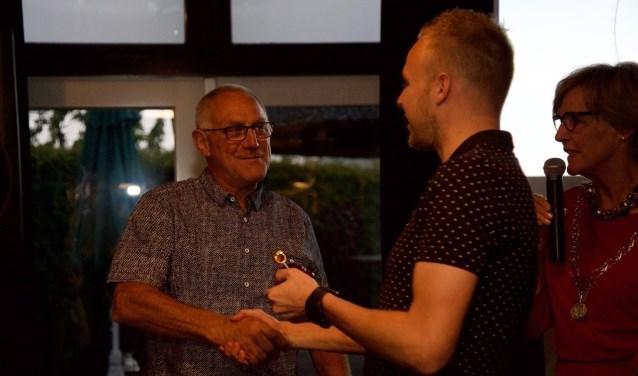 Michiel feliciteert zijn vader Tonnie Krabbenborg met de gouden fluit onder toeziend oog van burgemeester Bronsvoort. Foto: Lotte Bekkenutte