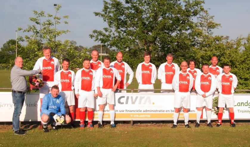 Omringd door leden van beide teams in de nieuwe outfit ontvangt Arjan Wanschers van Civra als dank een bloemetje uit handen van de SVBV sponsorcommissie. Foto: PR.