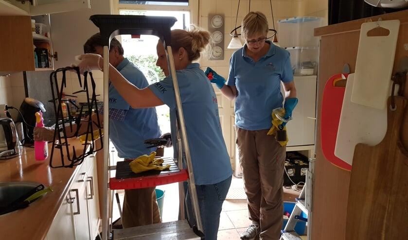 Drie vrijwilligers ruimen de keuken op en maken alles schoon
