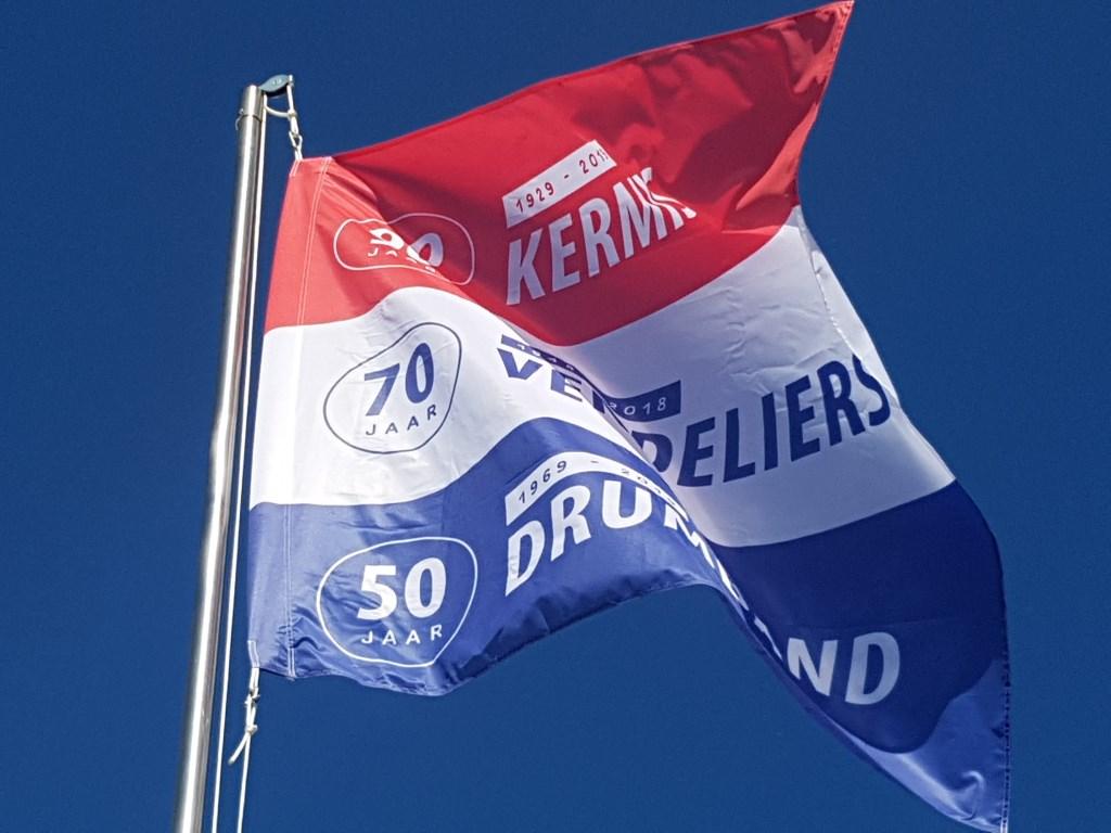 De speciaal ontworpen jubileumvlag wappert boven het kermisterrein in Lievelde.   © Achterhoek Nieuws b.v.
