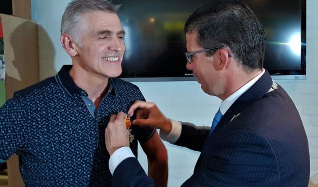 Burgemeester van Oostrum speldt Marcel Helmers de Koninklijke Onderscheiding op. Foto: Henri Walterbos