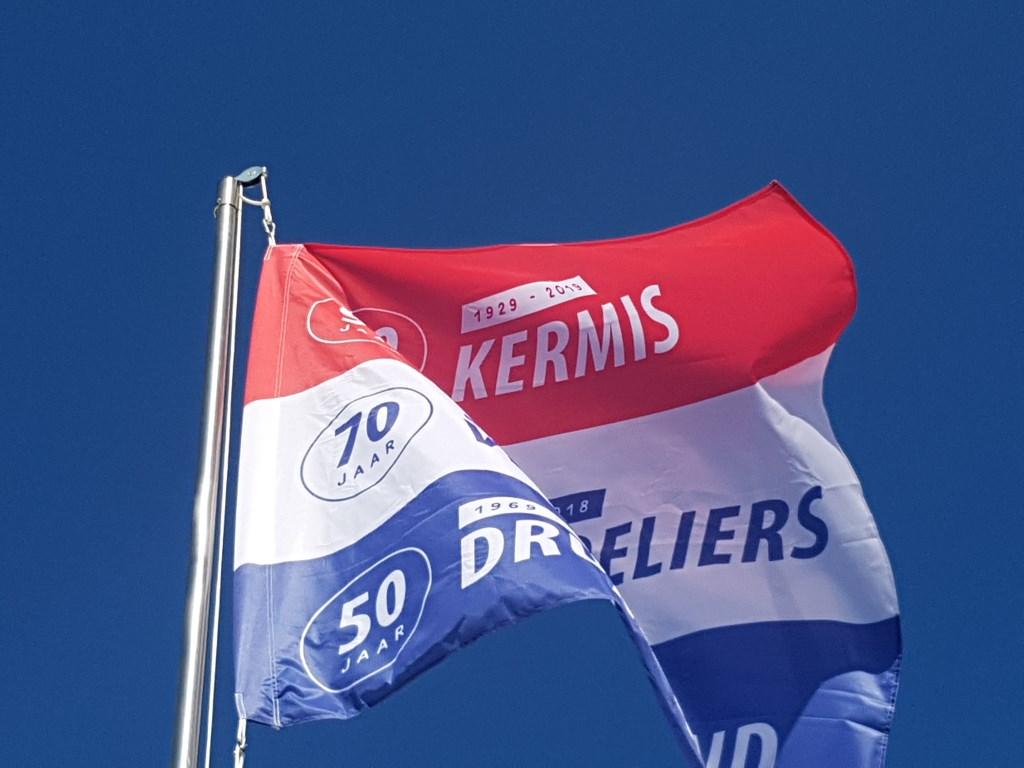 De speciaal ontworpen jubileumvlag wappert boven het kermisterrein in Lievelde  © Achterhoek Nieuws b.v.