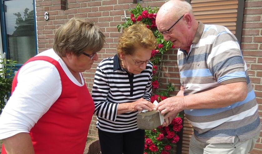 Wil Hondorp (rechts) geeft aan Toos Groenen (midden) en Annie Groenen uitleg over de unieke straatsteen. Foto: Josée Gruwel