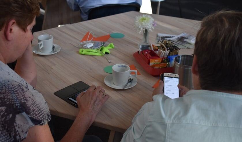 Twee bezoekers van de bijeenkomst kijken in de app hoe het staat met de toegankelijkheid.Foto: PR