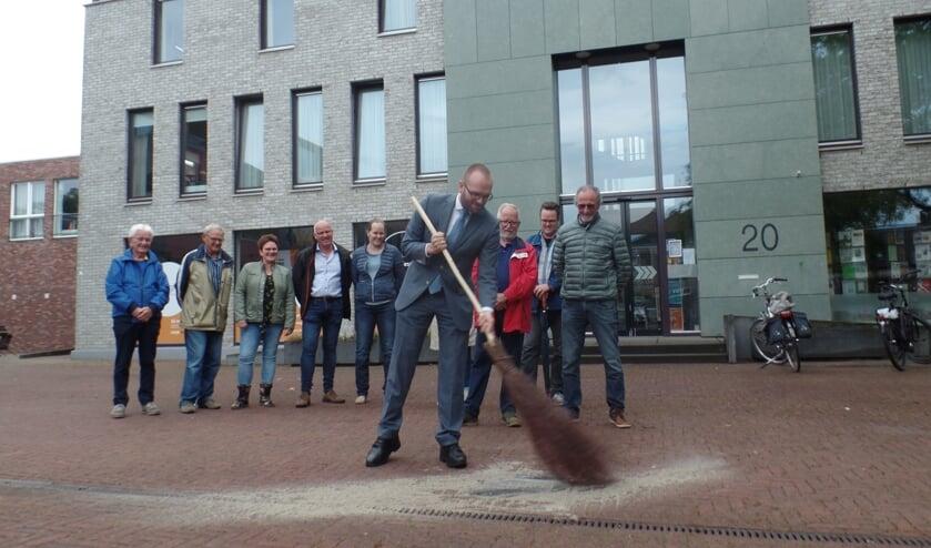 Met een aantal flinke vegen met een berkenbezem opende wethouder Gerjan Teselink op het Kerkplein de fototegelroute. Foto: Jan Hendriksen.