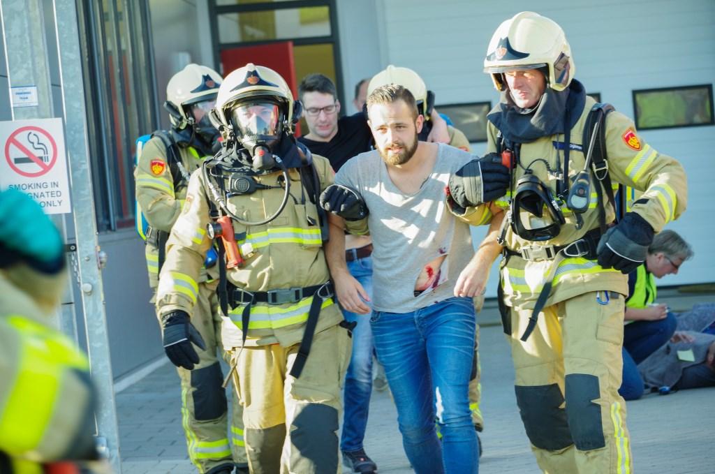 Brandweerlieden leiden medewerkers het pand uit. Foto: Marlie Nieuwenhuis  © Achterhoek Nieuws b.v.