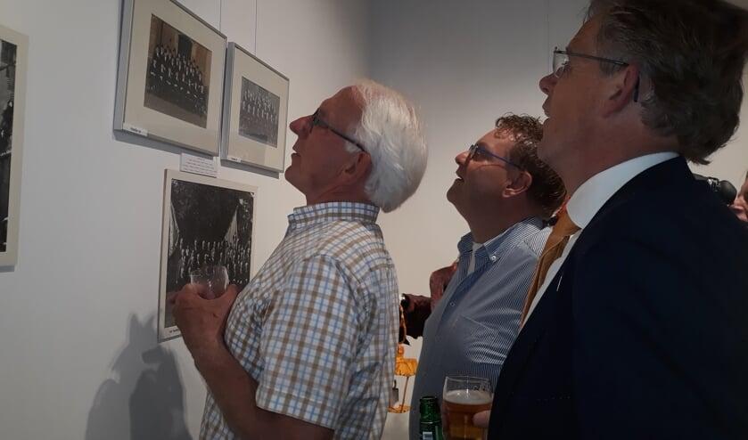 Bekenden zoeken op oude foto's. Rechts Hans Smit. Foto: Sis Huiskamp