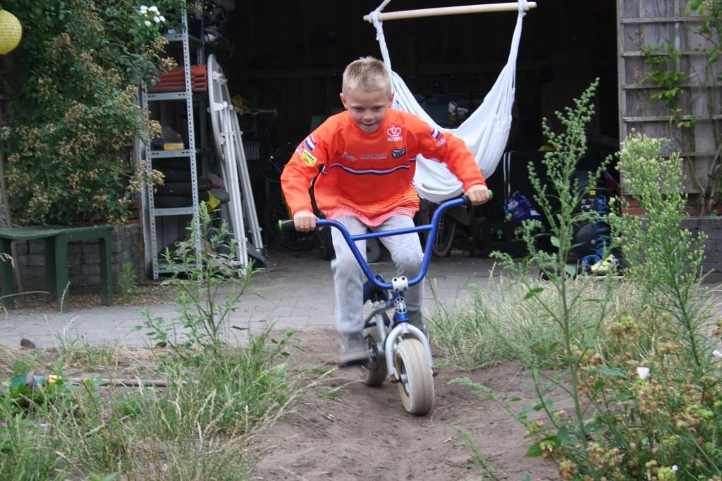 Stijn oefent op zijn oude fiets in de achtertuin. Foto: Verona Westera  © Achterhoek Nieuws b.v.