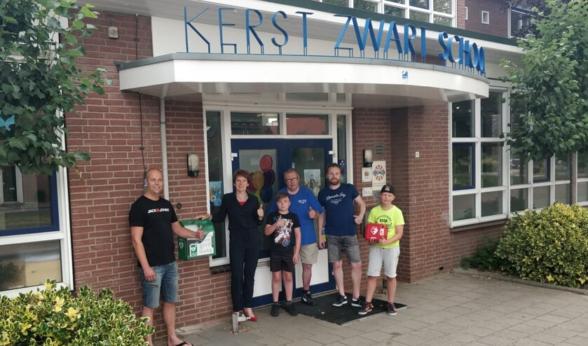 Andres Mol, Willemien van Uhm, Vince Bouwmeester, Jan Halfman, Maarten Gotink en Boet ter Bogt (v.l.n.r.) bij de nieuwe AED aan de Schoolstraat bij de Kerst Zwartschool. Foto: PR.