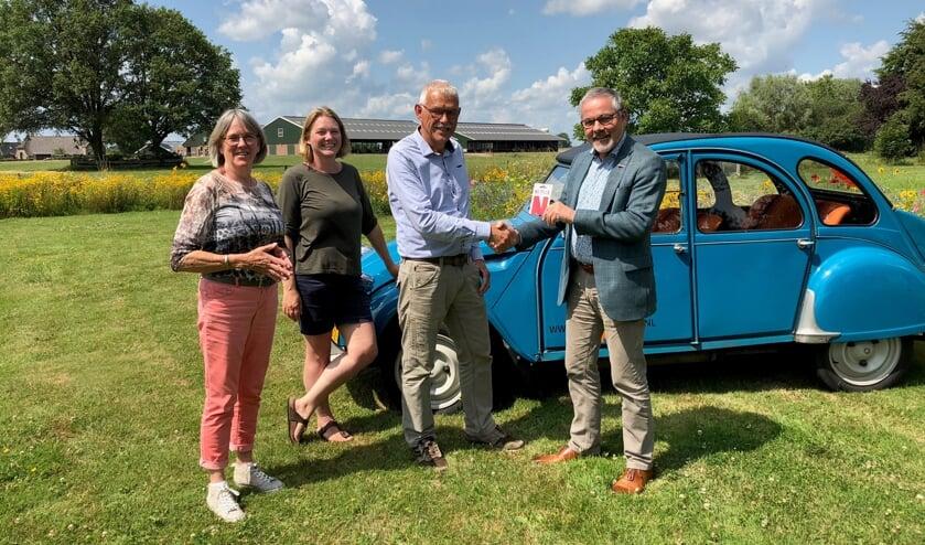 Wethouder Evert Blaauw (r.) overhandigt een Netflixcadeaukaart aan Ina, Dieuwke en Bertus Rietberg. Foto: PR