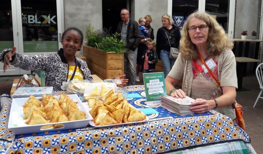Vol trots laat een van de deelnemers aan het Taalcafé de baksels zien. Foto: eigen foto
