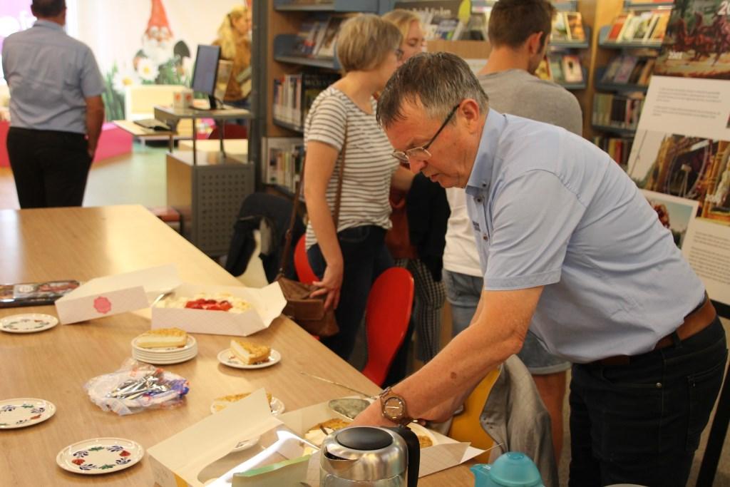 Terwijl de aanwezigen de panelen bekijken maakt voorzitter Herman zich nuttig door het gebak aan te snijden. Foto: Annekée Cuppers  © Achterhoek Nieuws b.v.
