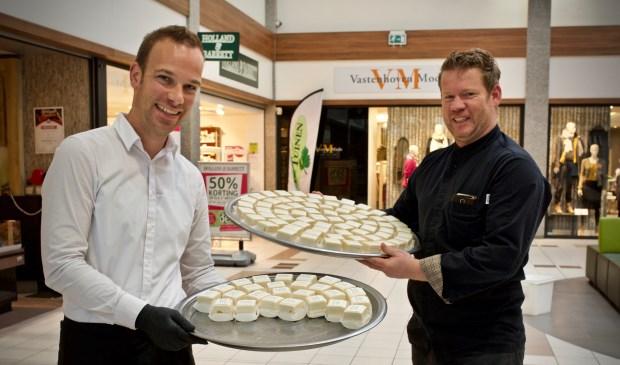 Dennis van Line-Up Events en John Hoetjes van Bakkerij Kees Zoon delen gebakjes uit aan het winkelend publiek.