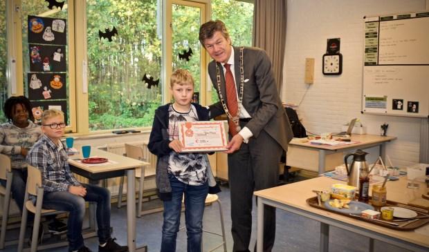Burgemeester Mans reikt de cheque uit aan Danny van groep 8 van de Antoniusschool