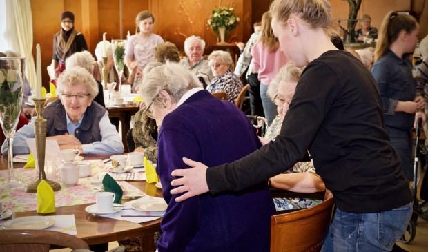 Een leerling van De Springschans helpt één van de bewoonsters van de Viva! Zorggroep bij het gaan zitten. Foto: Stip Fotografie