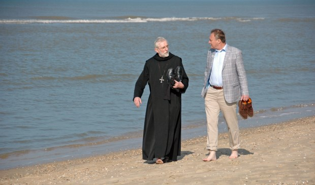 Leo en abt Mathijsen aan het strand.