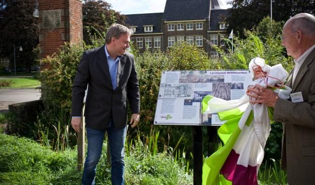 Wethouder Rob Opdam onthult samen met Fons Morsch het informatiebord Landgoed Willibrordus.