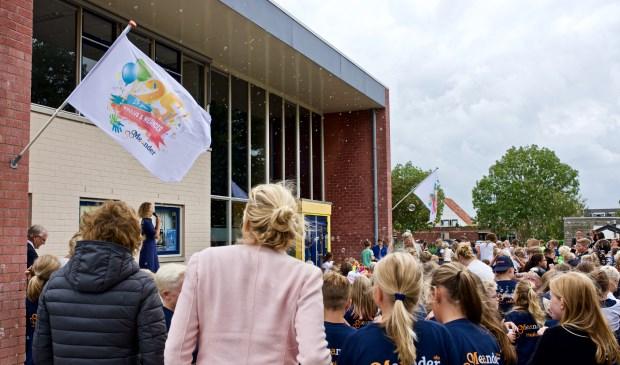 De feestvlag werd gehesen terwijl de kinderen met bellenblaas de vlag omhoog bliezen