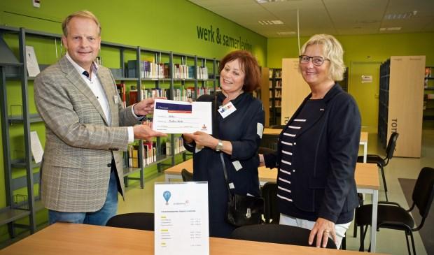 De cheque wordt uitgereikt door Ko Hemminga (Rabobank) aan Jeanette Braam en Ted Herkes (Bibliotheek Heiloo)