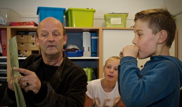 Eugène Vriend leert de leerlingen van de Paulusschool hoe je Kortjakje speelt op de mondharmonica.