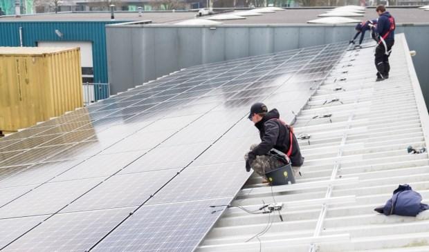 Energiecorporatie Cohesie installeert zonnepanelen op een gemeentelijk dak op de gemeentewerf,