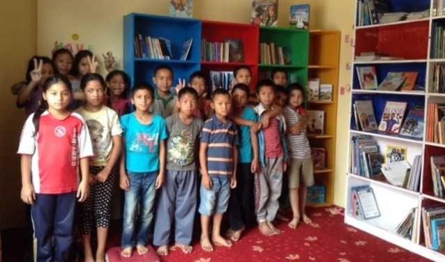 Nepalese kinderen in de blbliotheek van het tehuis