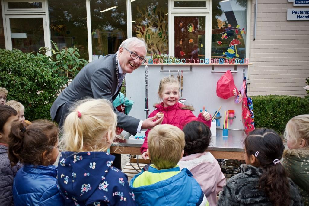 De burgemeester krijgt het eerste gebakje uitgereikt door Eline. Foto: STiP Fotografie © Uitkijkpost Media B.v.