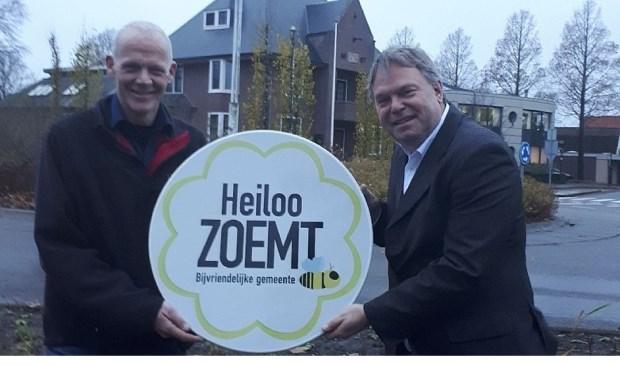 Wethouder Rob Opdam en wijkbeheerder Gerard Bak ontvangen het officiële bord 'Heiloo zoemt'. Deze krijgt een mooi plekje op de 'nieuwe' rotonde met plantvakken voor het gemeentehuis.