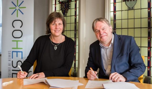 Voorzitter Wilma Eerenstein van COHESIE en wethouder Rob Opdam ondertekenen de overeenkomst.