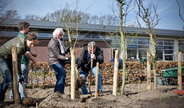 Wethouders Elly Beens en Rob Opdam helpen bij het planten van fruitbomen op Landgoed Willibrordus.