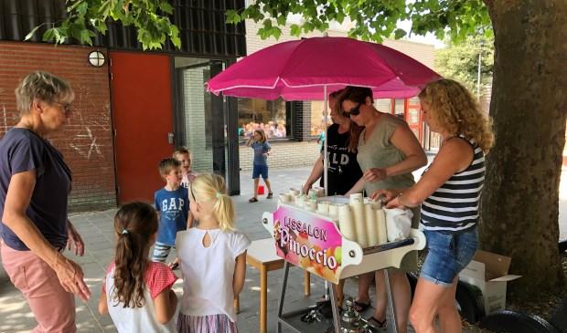De ouders van de ouderactiviteitencommissie voorzien de leerlingen van een overheerlijk ijsje.