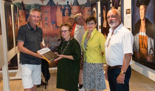Links Martijn Mulder die een prachtig boek overhandigt aan de gelukkige 2000e bezoeker. Verder vrijwilliger Carla Kager en Jos Hof op de foto.