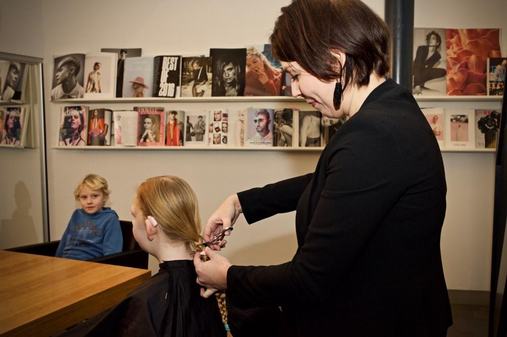 Carmen Sanders zet de schaar in het haar van Lies, broer Jeppe kijkt toe. Foto: STiP Fotografie © Uitkijkpost Media B.v.
