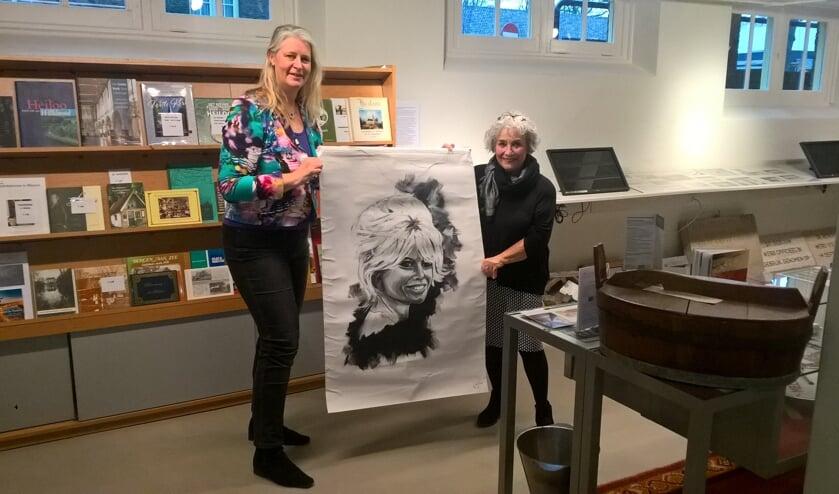 Josta de Graaf (r.) van de Historische Vereniging Heiloo overhandigt het kunstwerk aan kunstenares Jolanda Verduin.