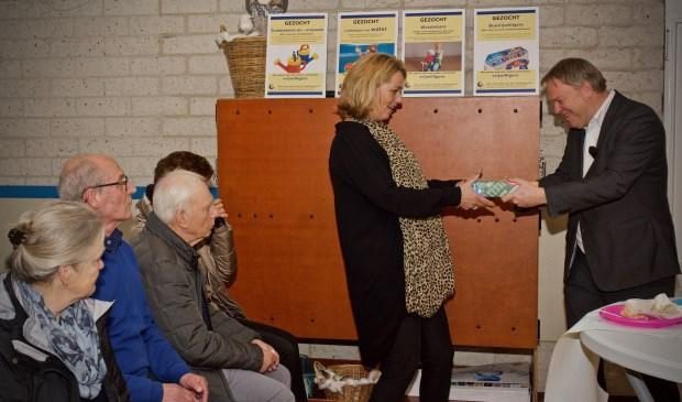 Wethouder Rob Opdam overhandigt een tablet aan Angelique Besseling.