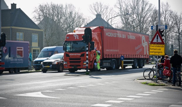 Een vrachtwagen mag de Stationsweg niet in. Een verkeersregelaar wijst hem de juiste weg.