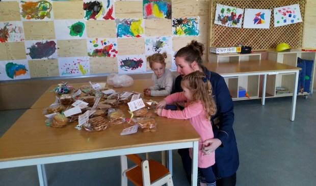 Phileine en Noortje zijn druk bezig met de verkoop van de koekjes
