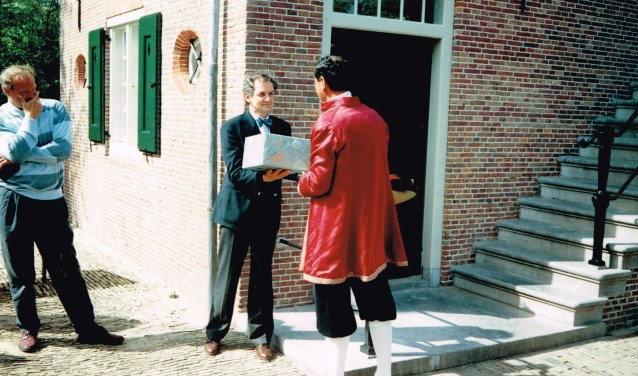 Er werd een cadeau overhandigd namens Het Bouwfonds;  wethouder Dinand de Ridder bekijkt het tafereel.