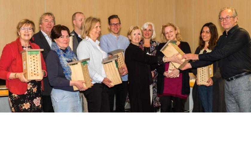 De Castricumse basisschooldirecteuren ontvangen uit handen van onderwijswethouder Ron de Haan de bijenhotels