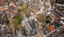De hoge Laurentiustoren met daarachter het kerkgebouw en de (besloten) tuin.